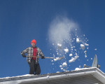 shoveller on roof with snow in the air against a blue sky
